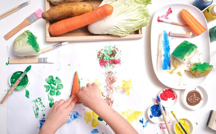 Small hands surrounded by paints and various vegetables