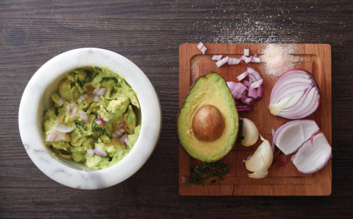 A halved avocado, red onion and garlic clove sit next to a bowl of guacamole