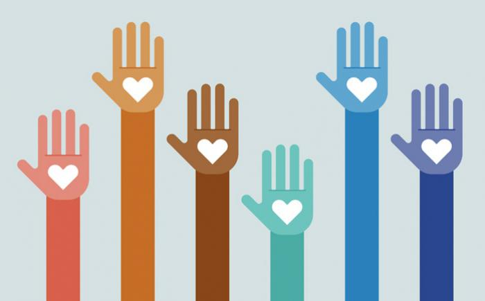 Raised hands of different colors have hearts on their palms