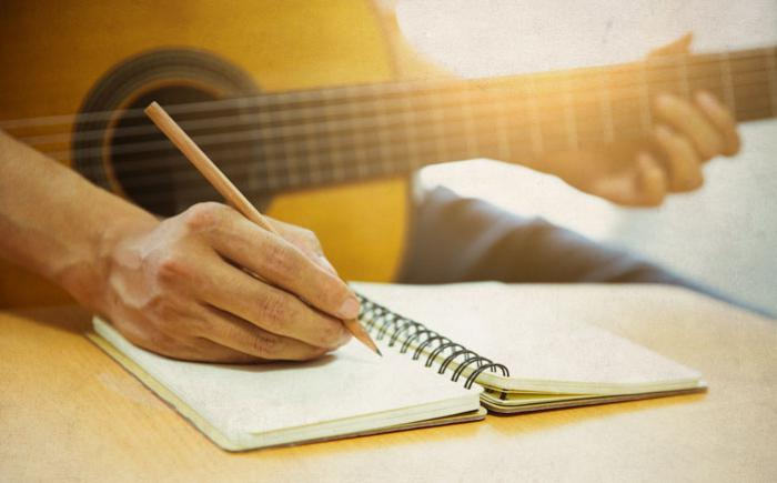 Man writing in a notebook, a guitar on his lap