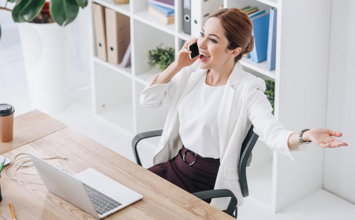 Happy businesswoman with laptop talking on cellphone