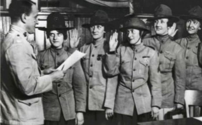 Man swearing in a group of women in military uniform
