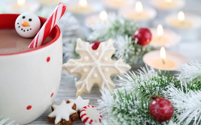 Wintry image of greenery, mug of cocoa and candles