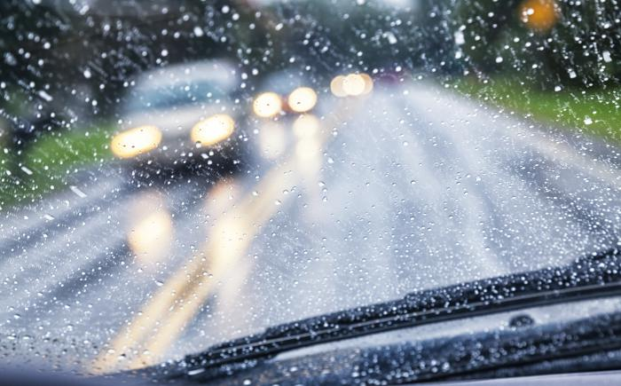 Looking out of rainy windshield at cars with headlights on