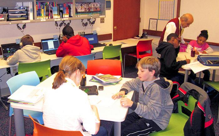 Students sitting at tables inside the Northwest Library Homework Help Center