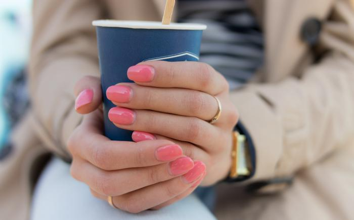 Woman's hands wrapped around paper coffee cup
