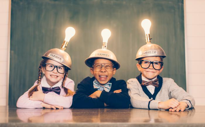 Elementary school-age kids wearing metal caps topped with light bulbs