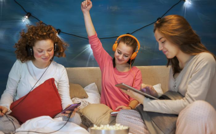 Three girls wearing headphones with smartphones and tablets