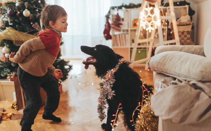 A child dances near a Christmas tree as his dog watches