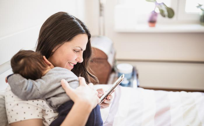 Woman holding baby and looking at a smartphone