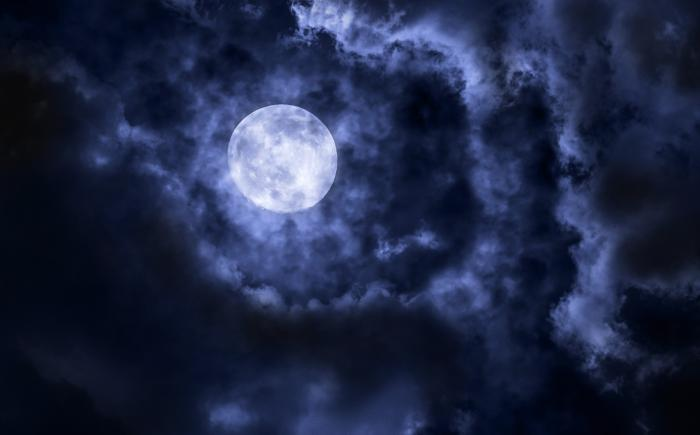 Photo of a full moon in a cloudy sky