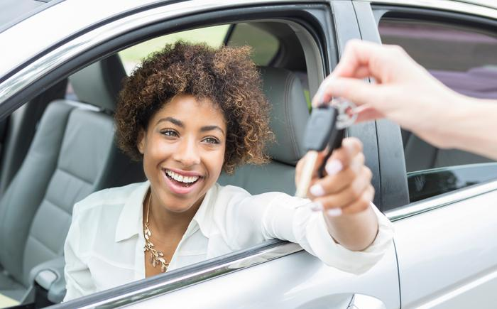 Young woman in a car taking car keys