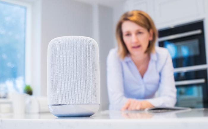 Woman at a kitchen counter with a voice assistant
