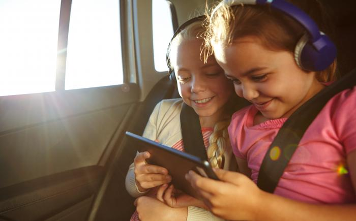 Two girls in a vehicle looking at a tablet