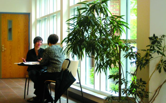 Two women seated at table in library lobby