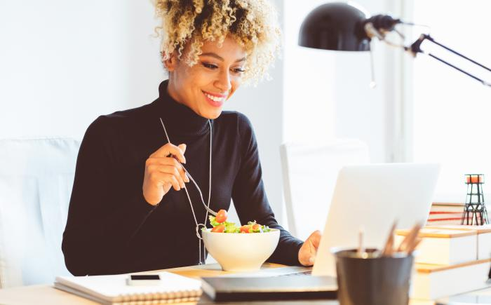 Woman eating salad and looking at a laptop