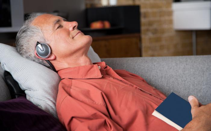 Man relaxing on couch wearing headphones