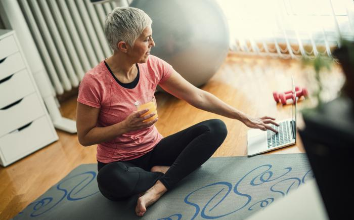 Older woman in workout clothes looking at a laptop