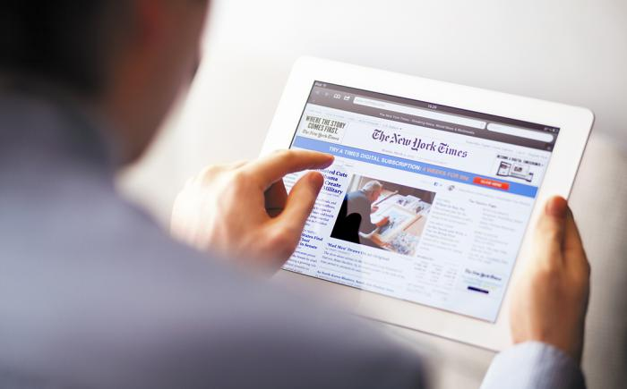 Man viewing the New York Times on a tablet