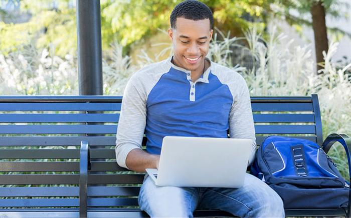 Young man on a bench outdoors with his laptop