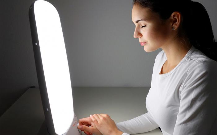 Woman using light therapy lamp with eyes closed
