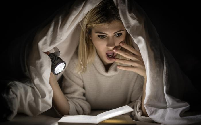 Woman reading scary book under cover with flashlight