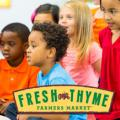 Woman reading to a diverse group of children, plus Fresh Thyme logo