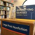 Signs that say: Magnifying glasses available here; and Large Print Nonfiction
