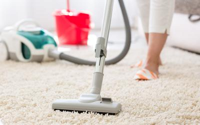 Person vacuuming a carpet