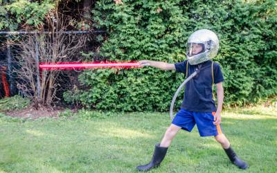 Boy holding red light saber and wearing foil covered helmet