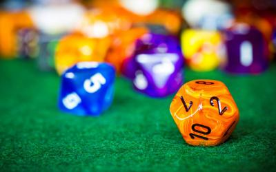 Colorful, 12-sided dice on green background