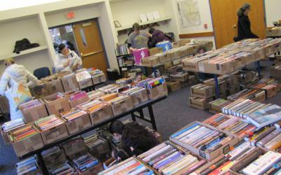 People browsing boxes of books on tables