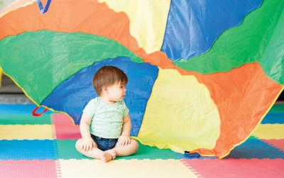 Small child in front of colorful parachute