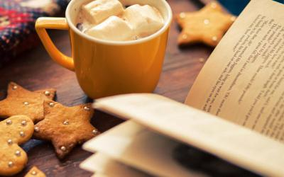 Image of mug of hot chocolate, a book and cookies