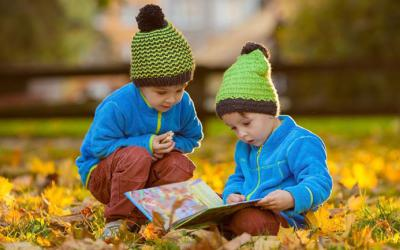 Two children reading a book outdoors