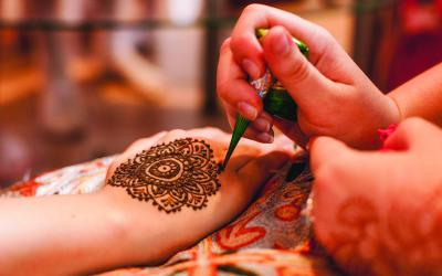 Hand holding a tube of henna to draw a geometric image on the hand of another
