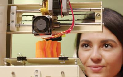 Young woman looking at a 3-D printer