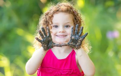 Smiling young girl with muddy hands