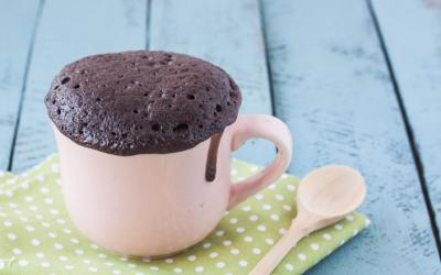 Chocolate cake in a white mug, with a spoon nearby