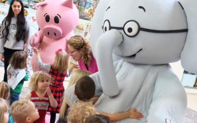 Young children with a pig and elephant costumed characters
