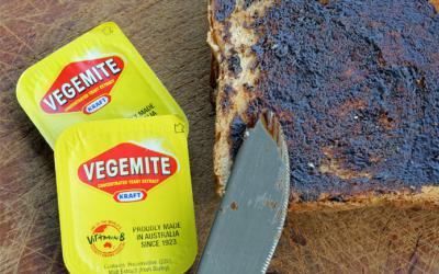 A knife spreading vegemite on a slice of bread and two vegemite packets