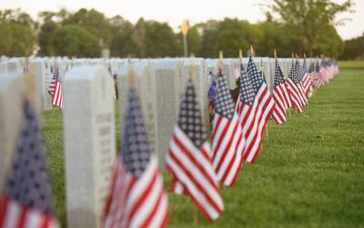 American flags in front of headstones at a cemetery