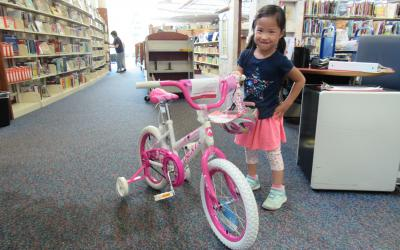 Haruka stands in the library next to a pink bicycle.