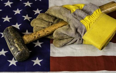 A sledgehammer and pair of gloves rest atop an American flag.