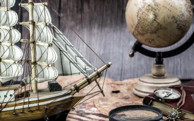 vignette of old sailing ship, globe, magnifying glass and compass