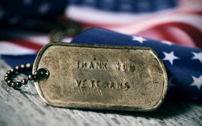 Military dog tags in front of an American flag