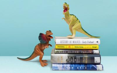 Dinosaur toys standing on stack of books