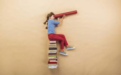 Girl sitting on a stack of books using rolled up cardboard as a telescope