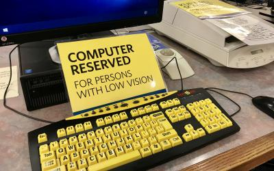 Sign that says: Computer reserved for persons with low vision