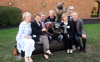 Library director and Board members pose with sculpture